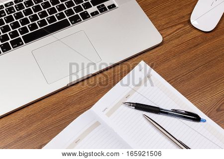 Notepad and laptop on wood table. View from above