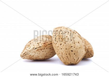 Closeup of three almonds isolated on white background.