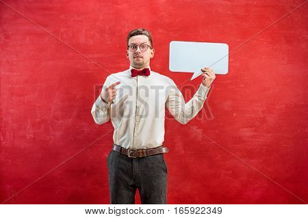 Young disappointed funny man with empty blank sign on red studio background with copy space
