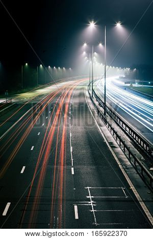 Long exposure of a UK motorway at night time with traffic trails illustrating cars driving on the left.
