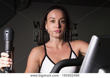 A young girl goes in for sports in the gym .Cardio workout.