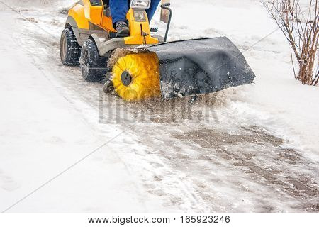 man cleans snow machines on winter day closeup