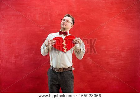 The young funny man with abstract broken and glued heart on red studio background. Concept - unhappy and happy love
