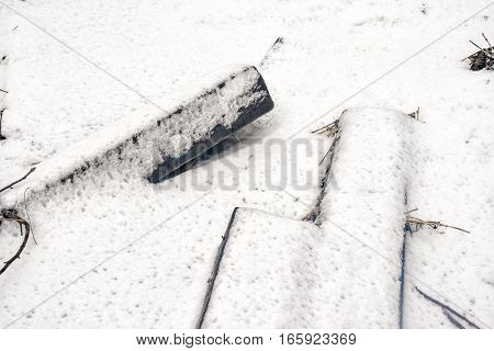 two wooden railway sleepers covered in snow on gloomy winter day