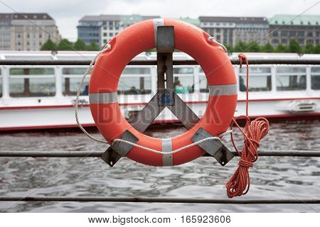 A life ring on the bank of the Alster Lake in Hamburg Germany. The location is popular with tourists who take sightseeing boats as seen in the background.
