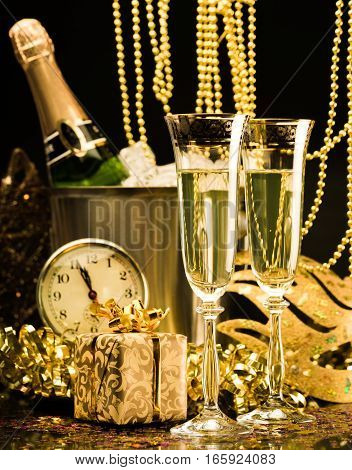 Bottle of Champagne with Flutes, Streamers, Mask, Gift Box and Clock Close to Midnight