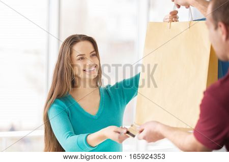 Smiling Woman Taking Shopping Bags and Passing a Credit Card