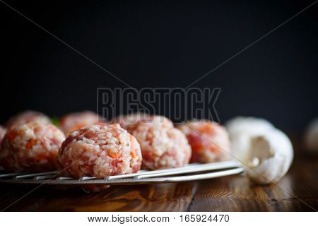 raw meatballs tangled meat with carrots on black background