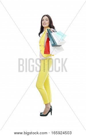 Studio portrait of a happy young woman carrying shopping bags against a white background