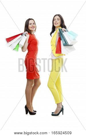 Full length studio portrait of a young women in red and yellow clothes with shopping bags isolated on white