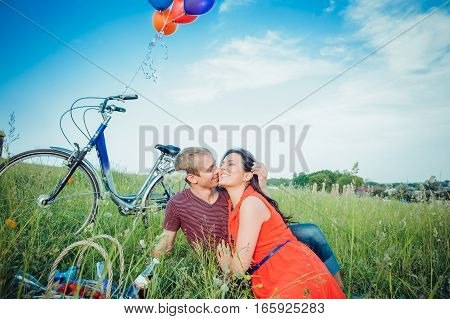 Happy Young Adult Couple In Love On The Field. Two, Man And Woman Have Picnic, Smiling And Resting O