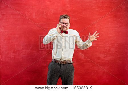 Portrait of puzzled man in glasses talking by phone on a red studio background
