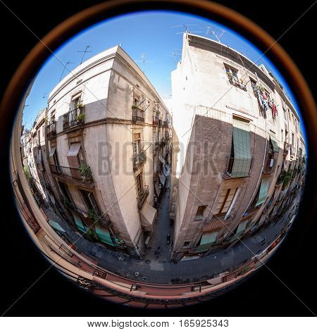 Fish eye view deep within the Gothic Quarter the old city of Barcelona Spain with its typical narrow alleyways and high apartment blocks.