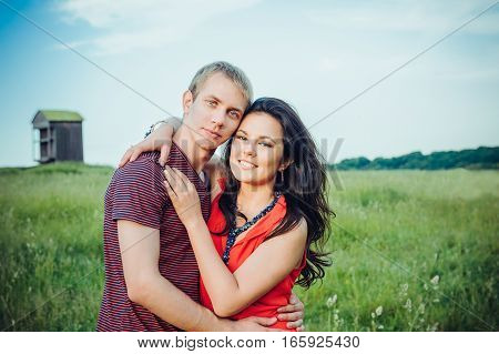 Happy Young Adult Couple In Love On The Field.