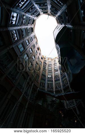 BARCELONA, SPAIN - SEPTEMBER 28 2006: Looking upwards within the atrium of a Gaudi design Barcelona apartment block.