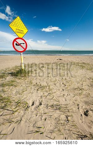 A sign at a sandy beach near Malahide Ireland warning people of the strong currents expected in the nearby waters.