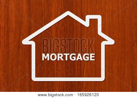 Paper house with mortgage word inside on wooden background. Housing family concept. Abstract conceptual image