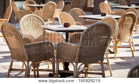 Outdoor restaurant with wicker chairs filling the view.