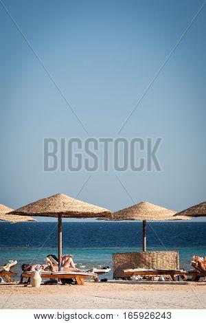 HURGHADA, EGYPT - NOVEMBER 21 2006: Tourists lazing on sun loungers on the coast of Red Sea near Hurghada Egypt.