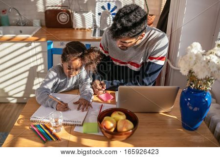 Father and daughter drawing at home in the kitchen.