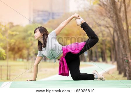 Beautiful mature woman show Yoga Half-Bow Pose - Ardha Dhanurasana at nature garden. Relax and active lifestyle concept soft focus in vintage tone