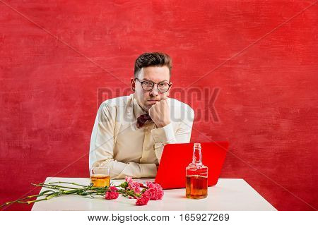The young funny man with flowers sitting with laptop on red studio background. Concept - unhappy love