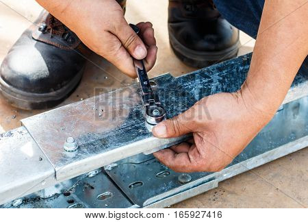 Mechanic holding a wrench, tighten the nut