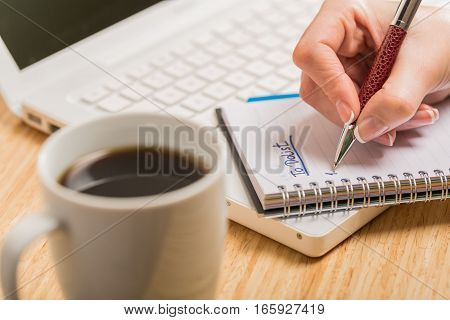 Closeup of a Person Writing a To Do List on Notepad