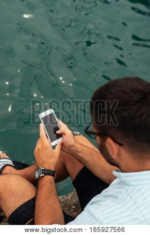High angle shot of a man texting on the coast.