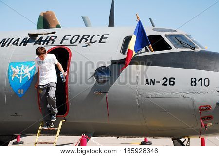 IZMIR, TURKEY - JUNE 5, 2011: This image shows a male spectator descend the stairs of the Antonov AN-26 aircraft during the 'Turkish Air Force 100th Anniversary' air show at 2nd Main Jet Base Cigli, Izmir Turkey.