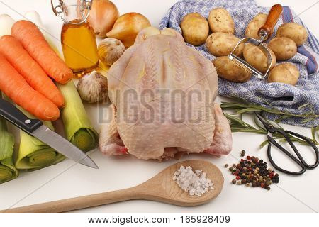 whole chicken celery carrot oil garlic potato coarse salt peppercorn and peeler on kitchen towel