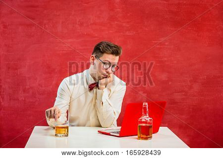The young funny man with cognac sitting with laptop at St. Valentine's Day on red studio background. Concept - unhappy love