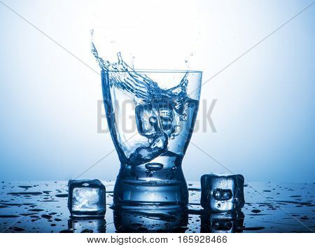 Splash water in a glass and pieces of ice