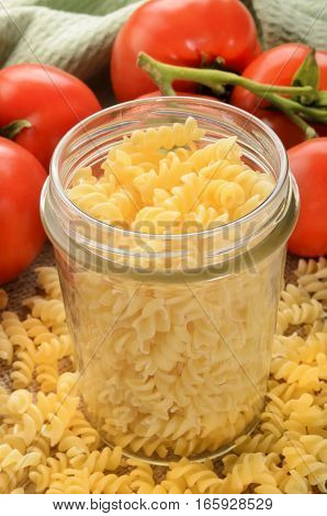 noodles in a jar and fresh tomatoes in the background