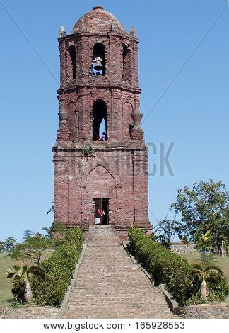 A tall very old bell tower made of adobe stones