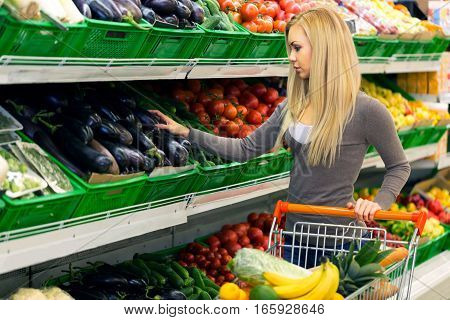 Portrait of a Woman Choosing Vegetables in a Supermarket
