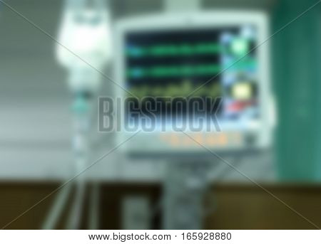 Drop of saline solution to help patient and medical monitors in a hospital blurred background.