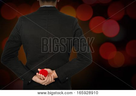 Man making proposal with wedding ring and red gift box on bokeh abstrack background.