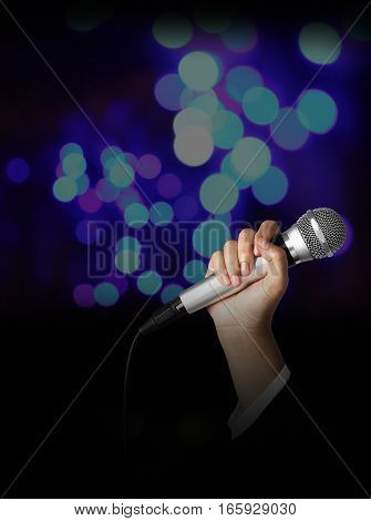 Businesswoman hand holding a microphone on blur of colorful bokeh background seminar concept.