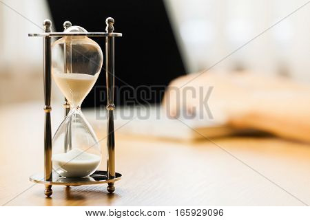 Closeup of a Hourglass with a Person Typing on a Laptop on Background