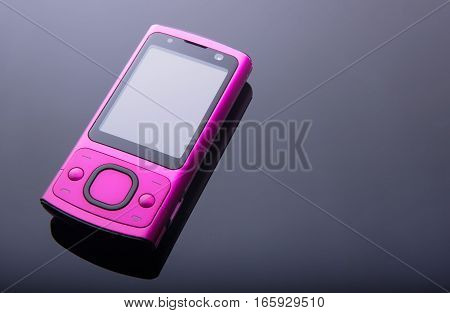Old pink mobile phone on gradient background