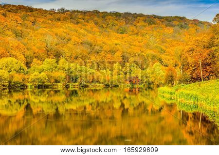 Fisherman's house on the lake in the autumn forest.