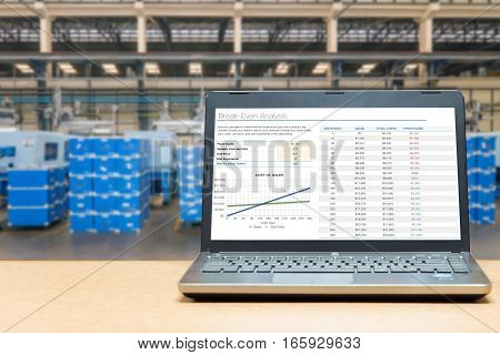 Laptop with analysis screen on table with blur warehouse cargo in factory. Smart factory concept.