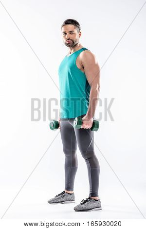 Full length portrait of sporty man exercising with dumbbells and looking at camera