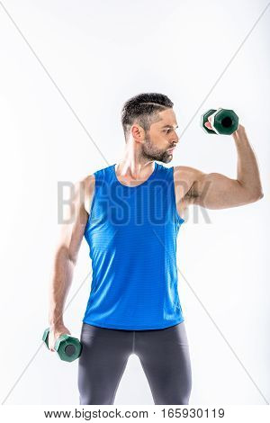 Muscular man in sportswear exercising with dumbbells on white
