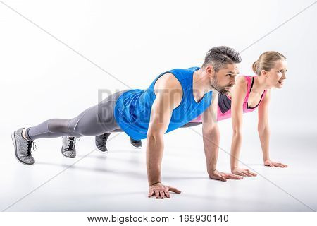Young sporty couple doing plank exercise together