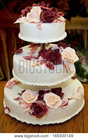 beautiful three-story wedding cake decorated with roses