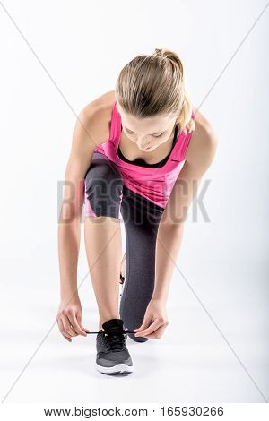 Young woman in sportswear tying shoelaces on white