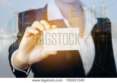 Double exposure of business woman hand showing a blank empty name card on city buildings background.