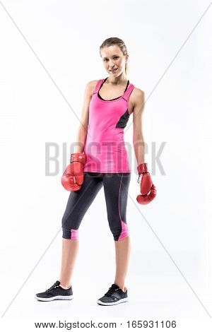 Young woman in boxing gloves posing and looking at camera on white